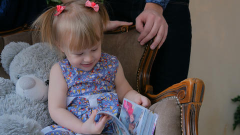 Little girl looking photobook at home Footage