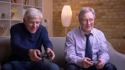 Portrait of senior male friends playing videogame one of them loses and gets Archivo
