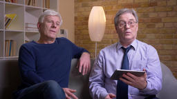 Portrait of senior male friends sitting together on sofa turn on the app on Footage