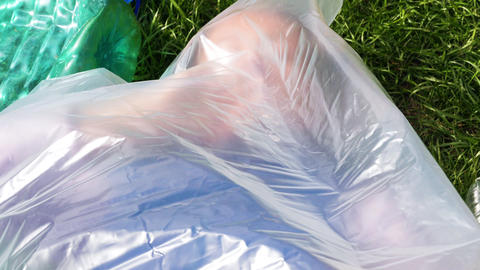 Woman is lying inside a plastic bag. Plastic pollution Footage