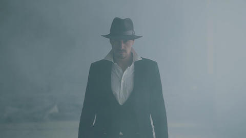 Portrait brutal gangster in fedora hat and classical suit walk from smoke. Slow Footage