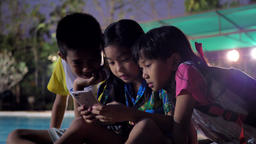 Asian children's group using smart phone relaxing near swimming pool in the evening Footage