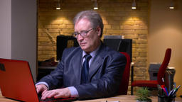 Portrait of senior businessman in official costume typing on laptop turns to Footage