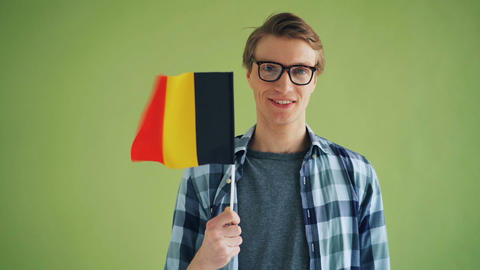 Slow motion portrait of cheerful person holding German flag and smiling Footage