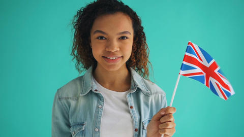 Slow motion of pretty mixed race woman holding flag of England smiling Footage