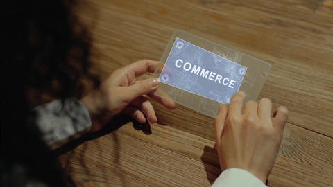 Hands hold tablet with text Commerce Footage