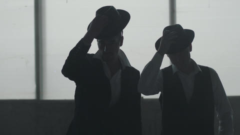 Two dark figures of confident well-dressed men in hats standing near each other Footage