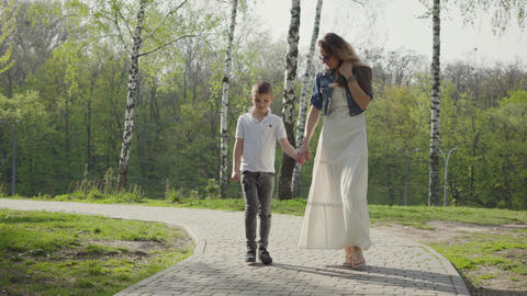 Mother walking with son in amazing green park. Outdoor recreation Live Action