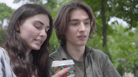 Portrait young happy couple in casual clothes spending time together in the park Footage