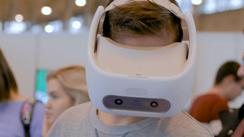 Man using virtual reality headset and looking around at VR exhibition GIF