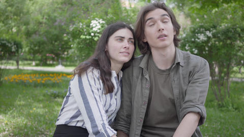 Portrait young couple in casual clothes sitting at the bench talking and holding Footage