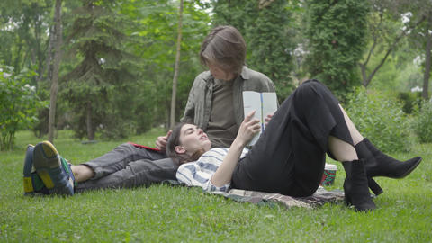 Young couple in casual clothes spending time together outdoors, having date. The Footage