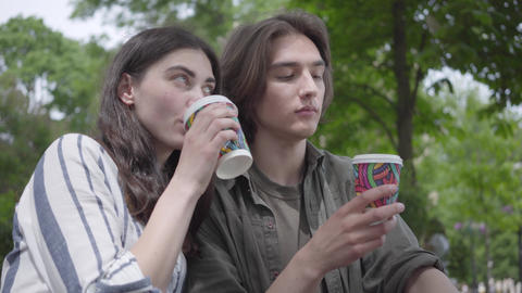 Young happy couple in casual clothes spending time together in the park, having Footage