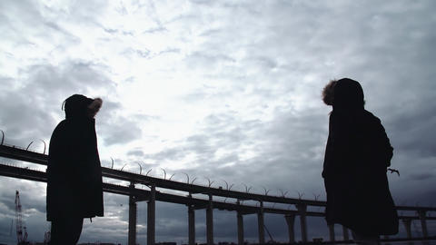 Two persons silhouettes standing on sea shore with highway bridge Footage
