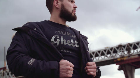 Bearded young man posing with jacket on shoulders, looking around Live Action