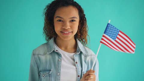 Slow motion of mixed race girl holding American flag smiling on blue background Footage