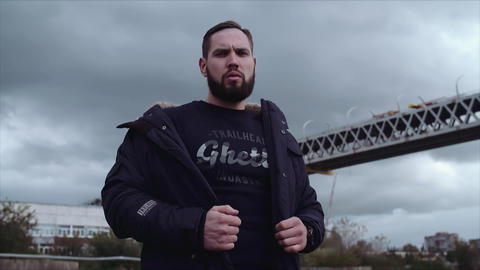 Well groomed bearded man holding parka on shoulders, looking around Live Action