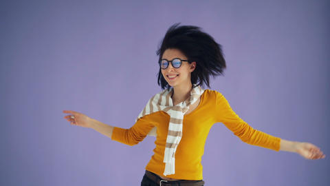 Slow motion of female hipster jumping moving head waving black hair having fun Footage