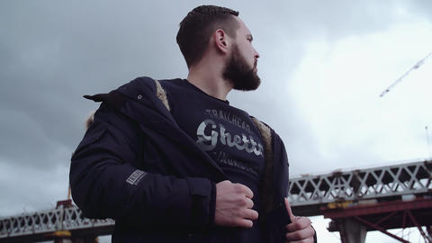 Bearded young man holding parka on shoulders, looking around Live Action