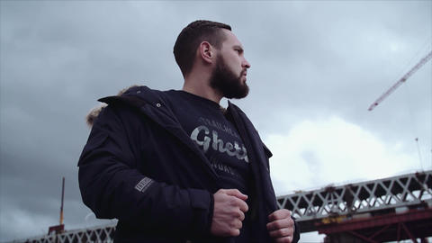 Bearded young guy holding parka on shoulders, looking around Live Action