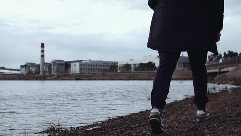 Legs of man in stylish sneakers walking on rocky shore at urban area Footage