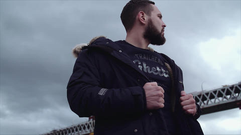 Well groomed bearded man holding jacket on shoulders, looking around Live Action