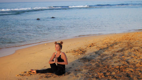 lady in black tracksuit sits meditating against waves Footage