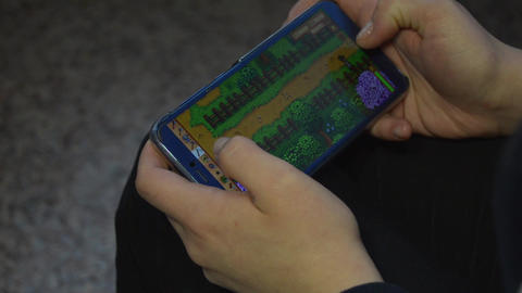 Girl playing a game on a smartphone Live Action