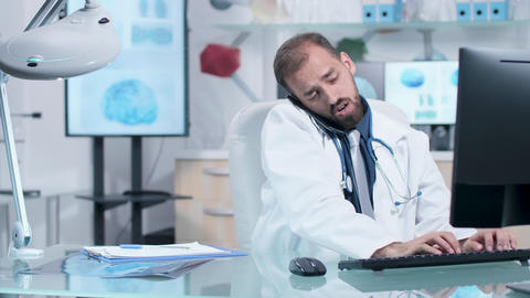 Doctor in his modern office talking on the phone Footage