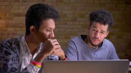 Closeup shoot of young indian and african american young male friends watching a Footage