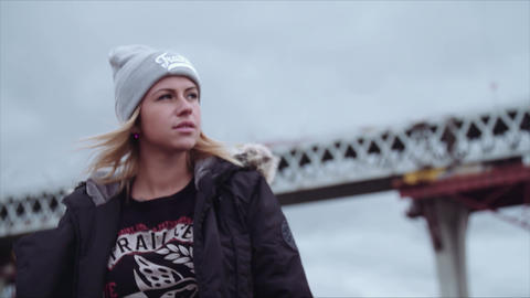 Young blonde pretty woman puts on hood of jacket, metal harbor structure Footage