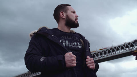 Well groomed bearded male model holding jacket on shoulders, looking around Live Action