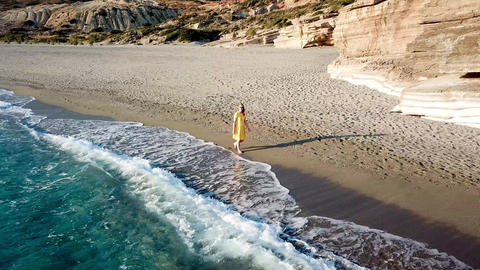 Aerial Drone Footage of a girl walking along a lonely beach Footage