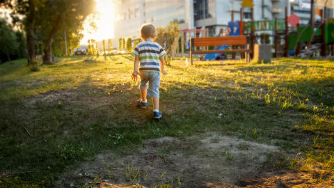 Photo of little toddler boy running on the grass at park against beautiful Photo