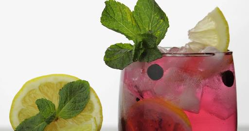 Glass with cold red drink with leaves of mint, lemon, black currants and ice Photo