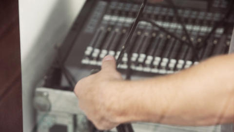 Man's hands are holding black cables on blurry background of electronic stuff Live Action