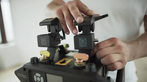 Guy's hands are setting different things on black plastic device in room Footage