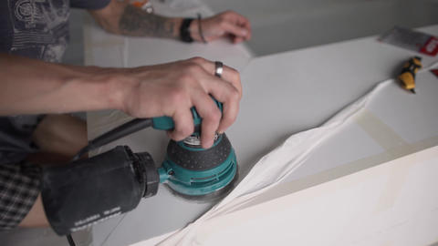 Man's hand is holding electronic green polisher and working on white surface Footage