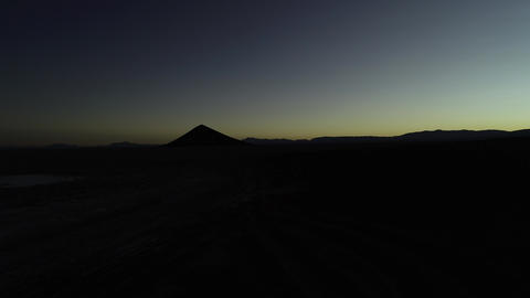 Aerial drone scene of silhuette of mountains and natural perfect piramid at sunrise. Black and Footage