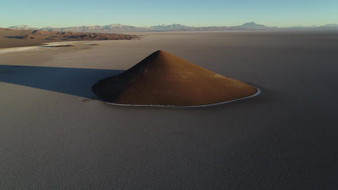 Aerial scene flying around natural pyramid at white and salar, general view of impressive cone. Live Action