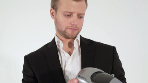 Blonde man in suit holds grey toy car in hands and stares at it with puzzle look Footage