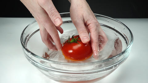 Female hands wash one ripe red tomato in a bowl of clean water at white Archivo
