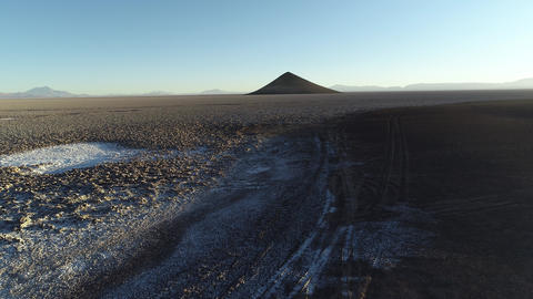 Aerial scene flying from the floor towards natural pyramid at white and salar, general view of Footage