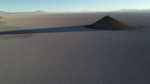 Aerial scene flying towards natural pyramid at white and salar, general view of impressive cone. Live Action