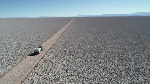 Aerial drone scene of 4x4 with caravan traveling along white wide salar with. From detail of car Footage