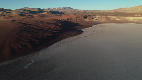Aerial drone scene of limit of white salar with brown desertic mountains. General view of eroded Footage
