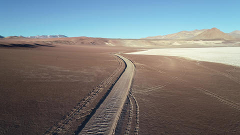 Aerial drone scene flying over off road track on limit with desert and salar landscape. Brown eroded Footage