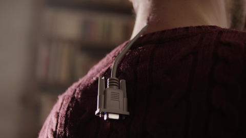 Grey D-sub cable is organically hanging from back side of human's neck Footage
