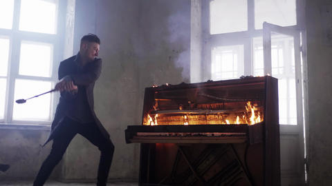 Young man in grey coat hits classic burning wooden piano with huge hammer Footage