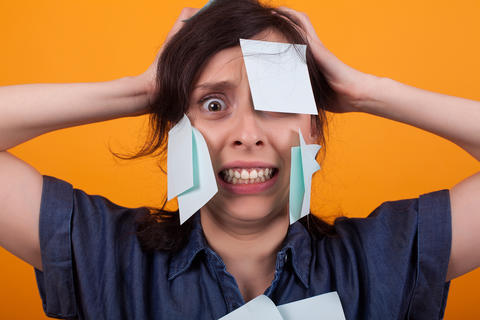 Portrait of beautiful woman frustrated with sticky notes on forehead in studio Photo